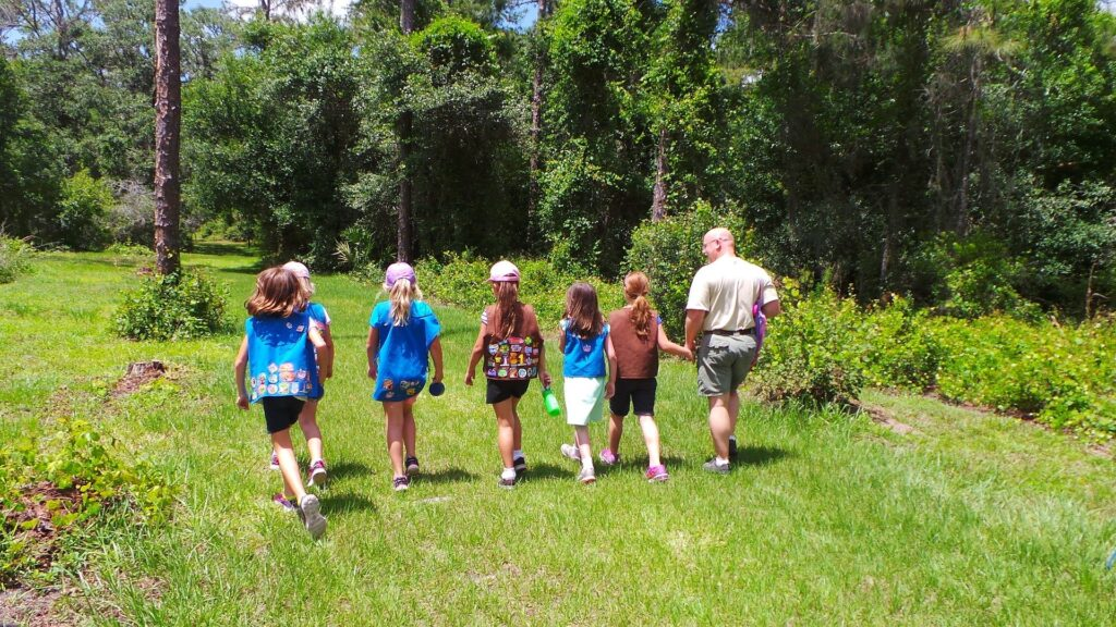 girl scouts walking in the grass