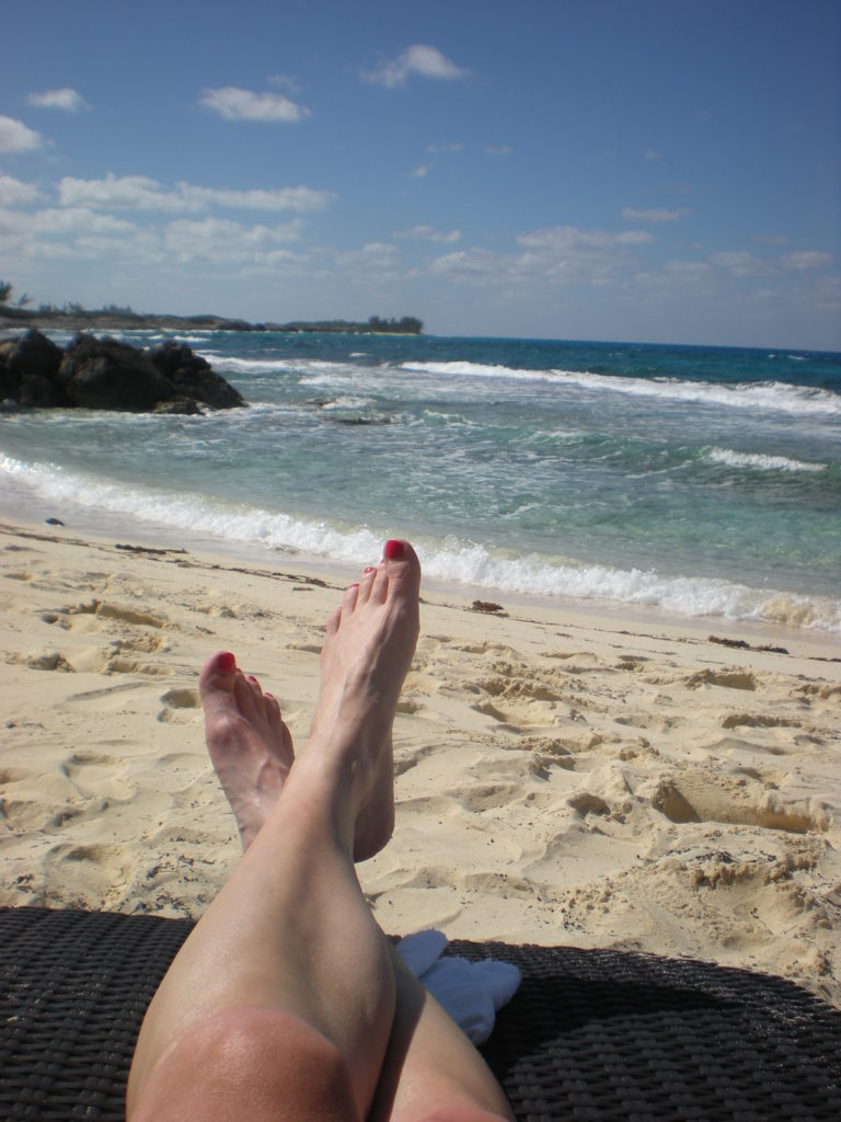 feet up and relaxing on the beach