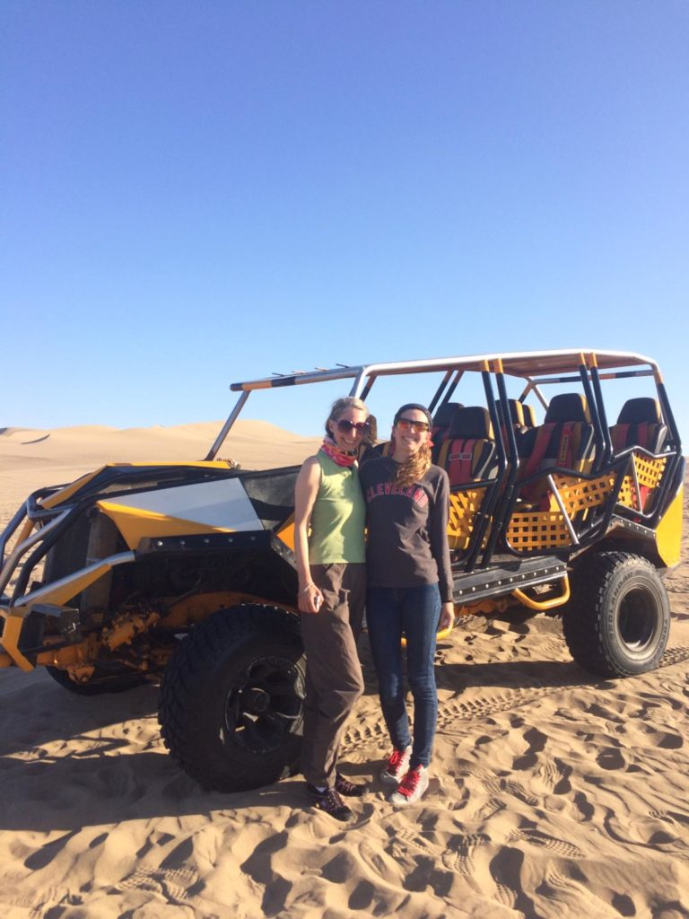 Posing with our dune buggy before sand boarding in Huacachina, Peru