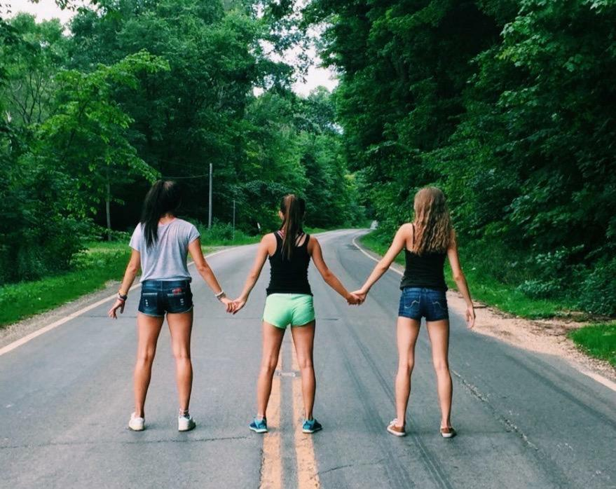 3 girls standing in the middle of the road holding hands