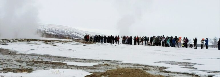 crowd of people around steaming Strokkur geysir in Iceland along Golden Cirlce driving route