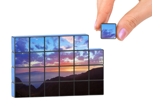 Hand putting together puzzle piece in a scenic photo puzzle