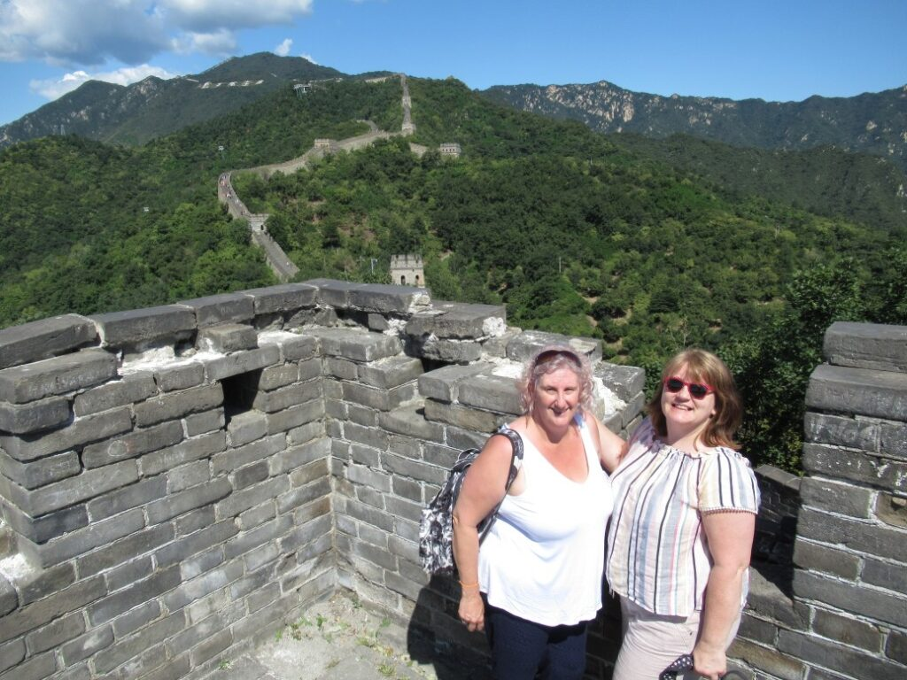 2 ladies posing on the great wall of china to celebrate their 50th birthday