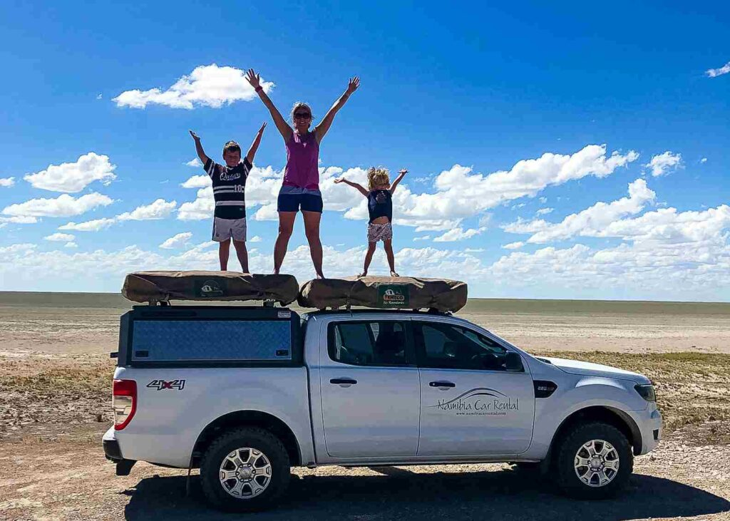 family on top of camper in Africa