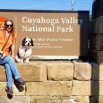 lady and dog sit at the Cuyahoga Valley National Park sign