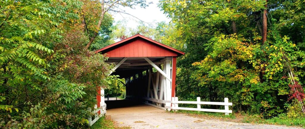 red covered bridge surrounded by green trees in cuyahoga national park