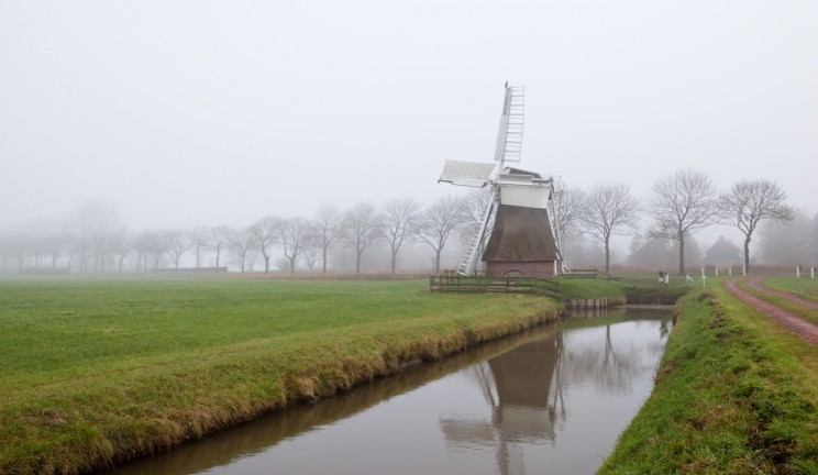 windmill on the edge of the water in the netherlands