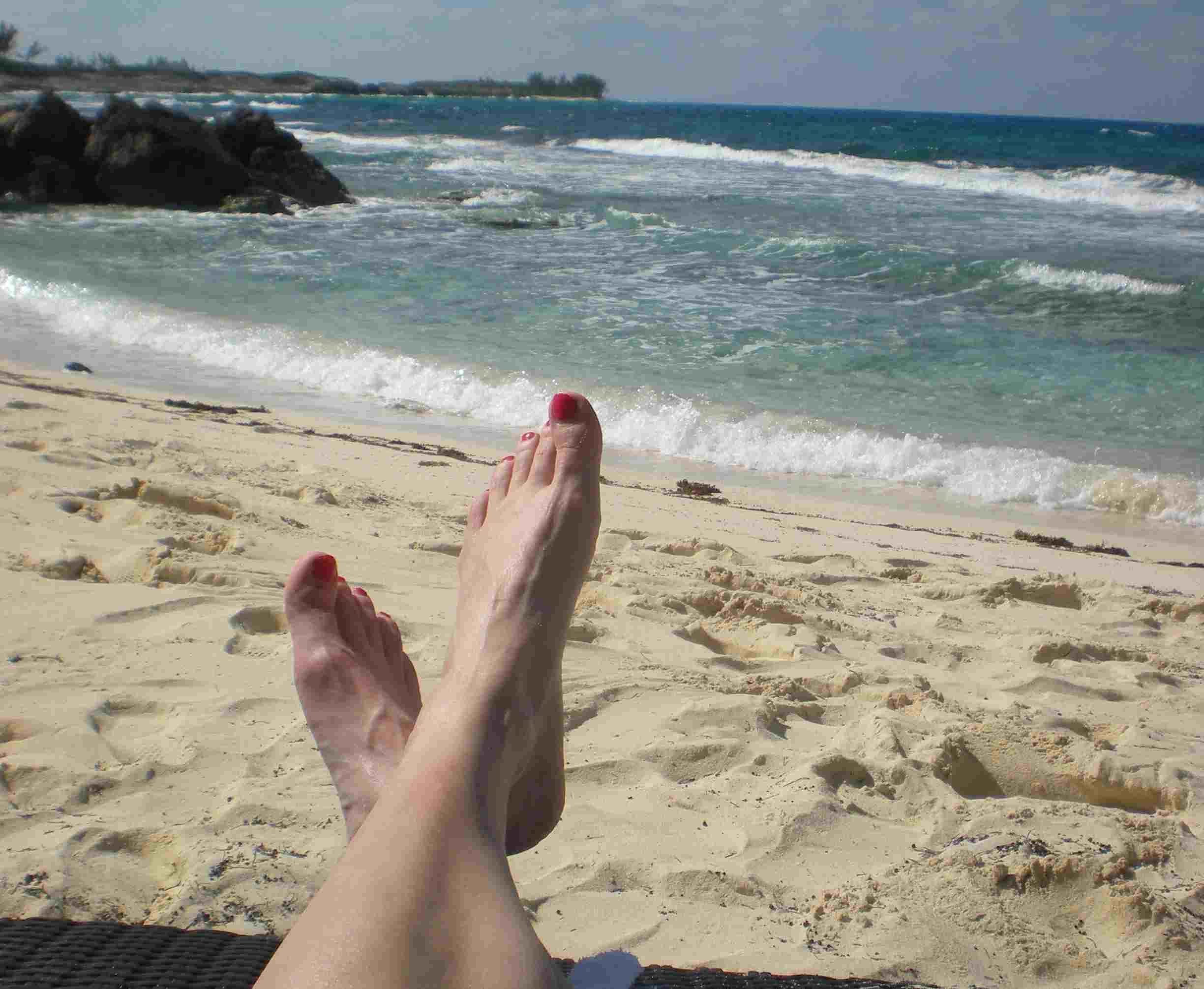feet propped up on a beach during a stress-free vacation
