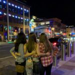 three girls standing and admiring the lights on broadway on a Nashville weekend trip