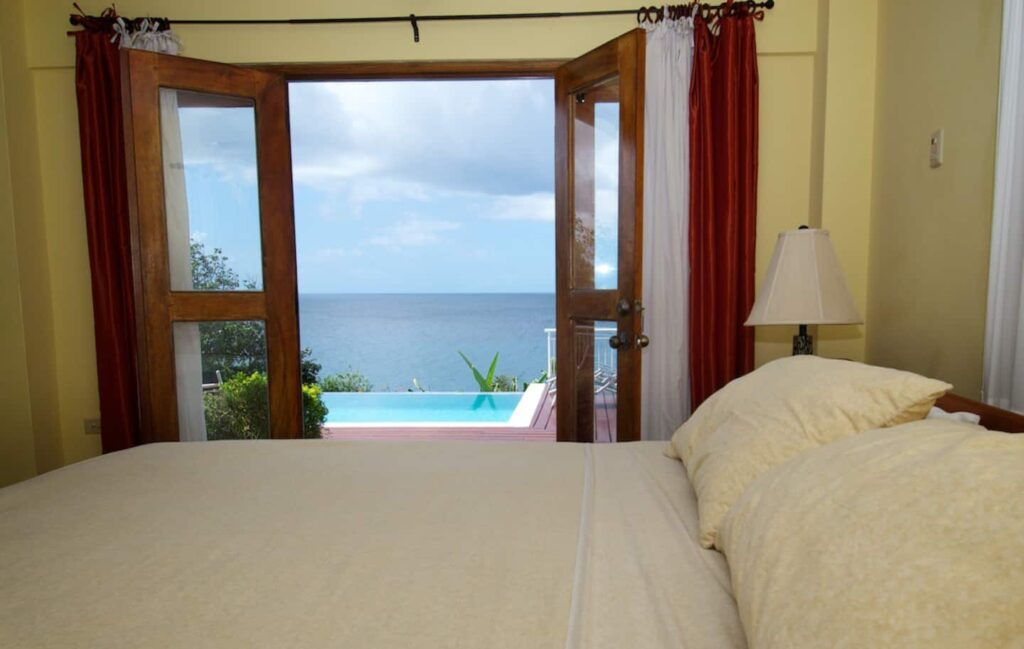 bedroom overlooking the pool and the sea at Mot Mot Luxury Lodge-bedroom - guest houses in Tobago