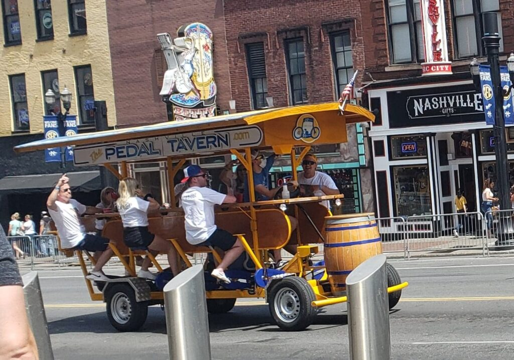 group of people seating on Pedal Bar going down the street in Nashville