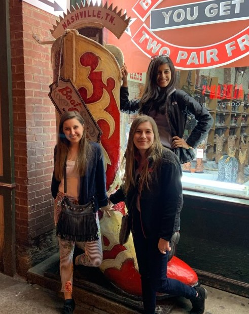 three girls posing by a boot in Nashville on a weekend trip