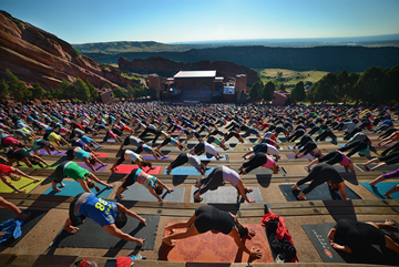 lots of people doing yoga at red rocks in a yoga pose on the bleachers