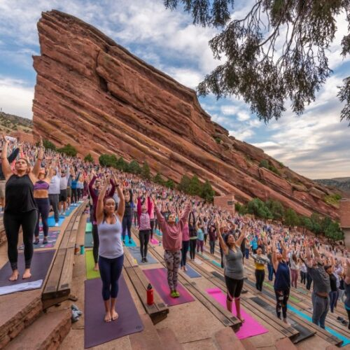 lots of people doing yoga at red rocks in Denver colorado