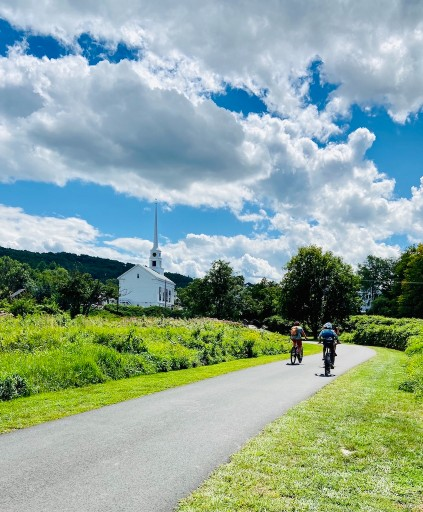 biking past a church on a grownup getaway in Stowe Vermont
