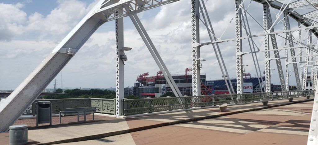 view of downtown nashville and stadium from pedestrian bridge over Cumberland River