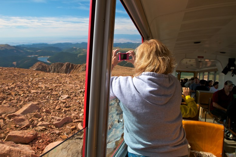 woman looking out a train car at mountain scenery from the Pikes Peak Cog Railway