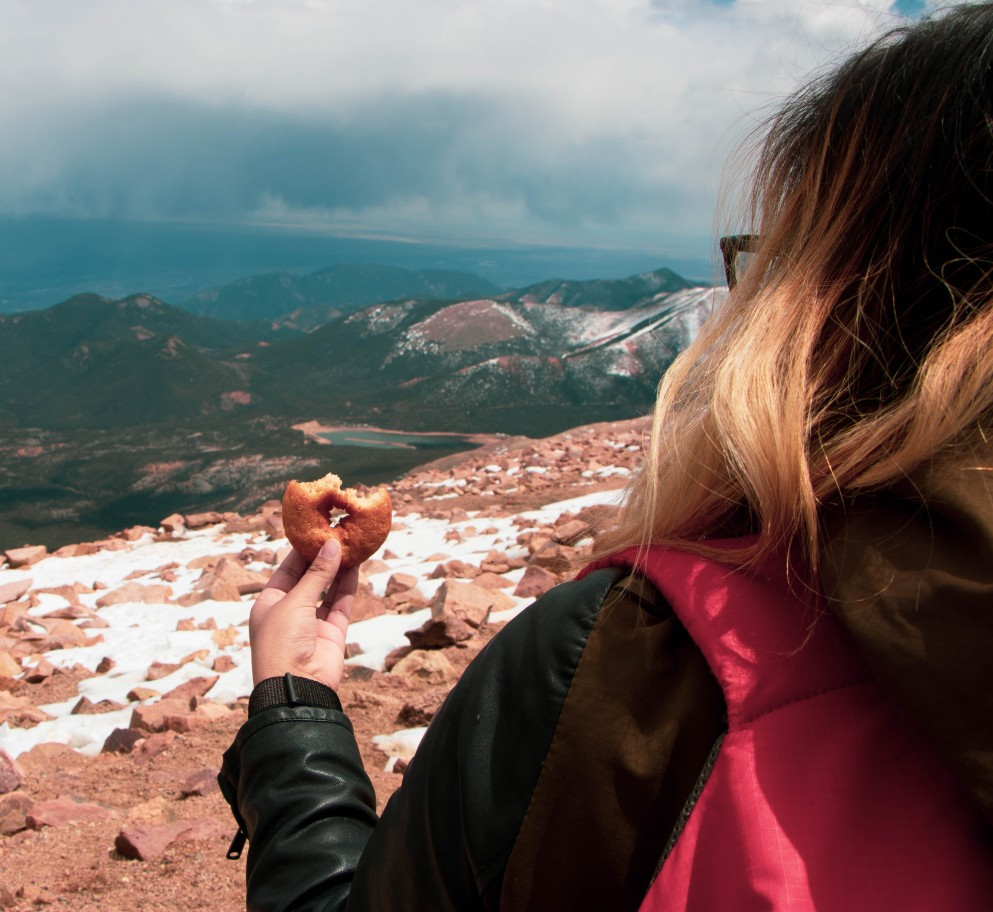 woman holding donut at the top of Pikes Peak