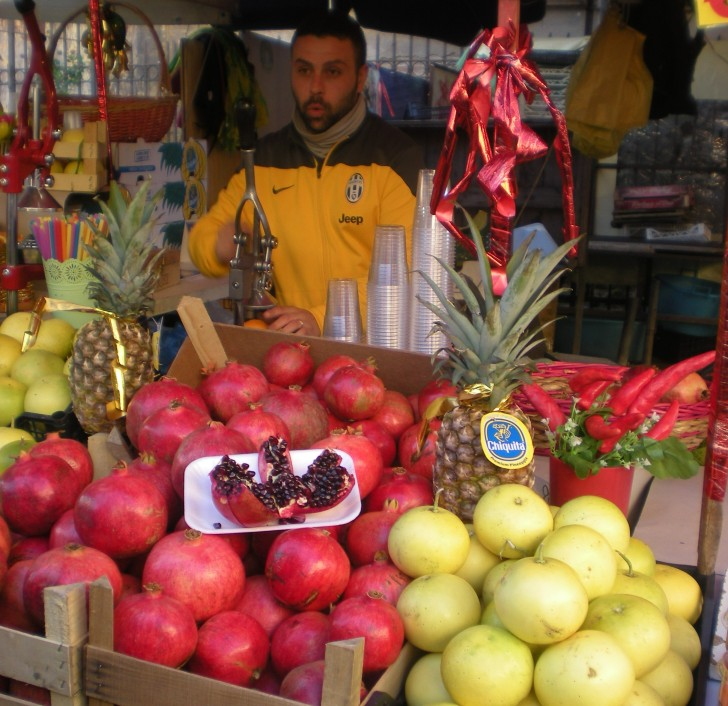 man selling Pomegranites at the Palermo Market