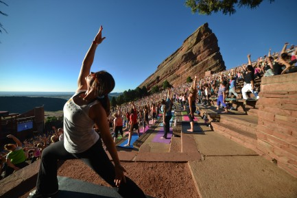 woman stretching in yoga pose in from of lots of people doing yoga at red rocks in denver colorado
