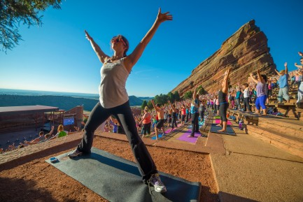 woman stretching with arms outstretched in yoga pose in from of lots of people doing yoga at red rocks in denver colorado