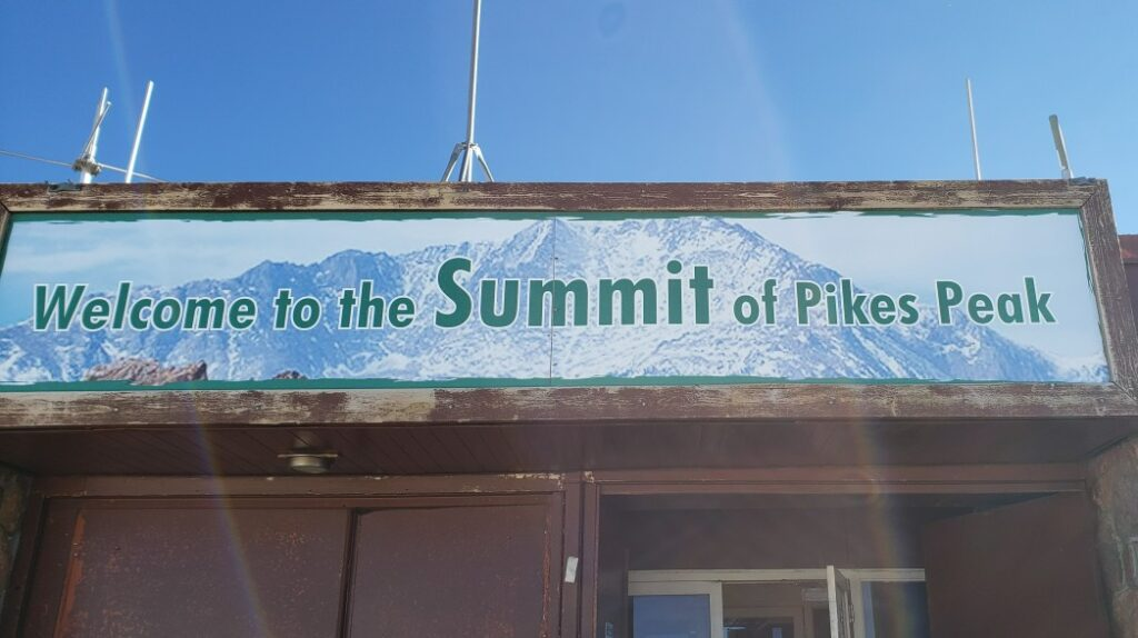 welcome to the summit of Pikes Peak Sign on the building after driving Pikes Peak