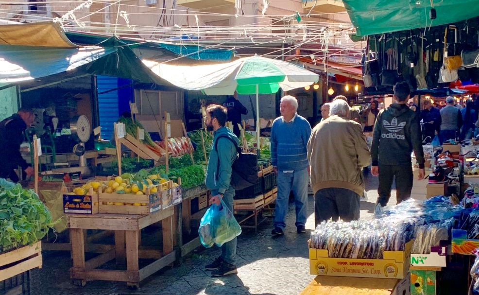 colorful stalls and vendors selling lots of food at the Palermo street food market
