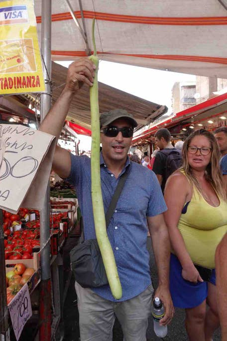 man holding up a long zucchini at a Palermo street food market