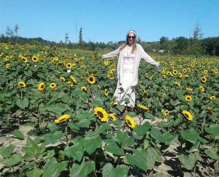 lady standing in a sunflower field in ohio with arms spread wide in happiness