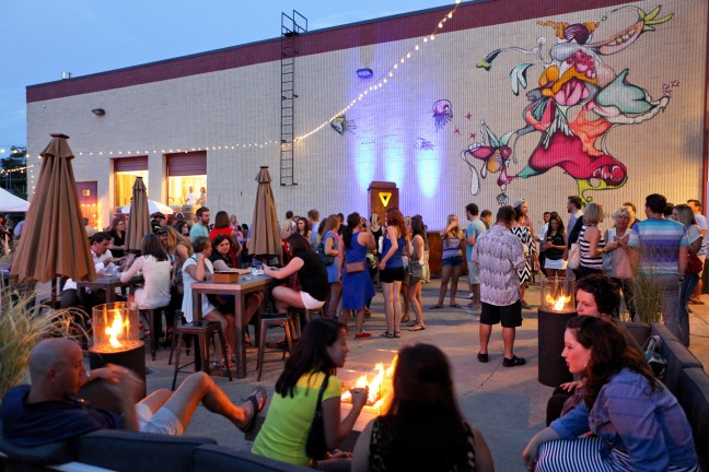 gathering of people socializing in front of colorful street mural