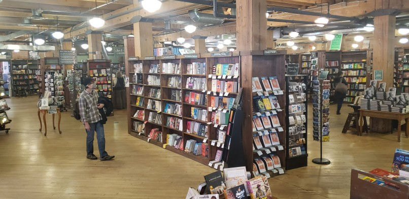 people shopping in bookstore with shelves lined with books in Denver