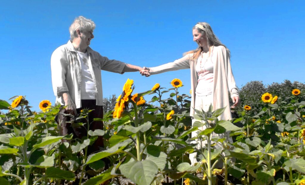 mother and daughter holding hands in a sunflower field