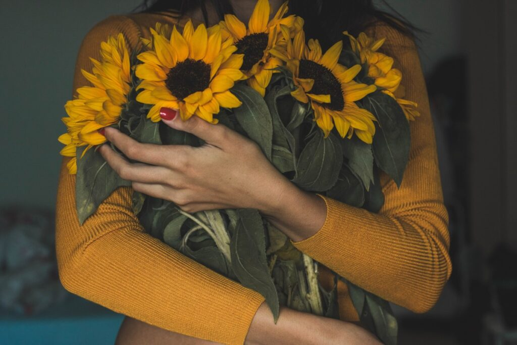 holding a bouquet of sunflowers