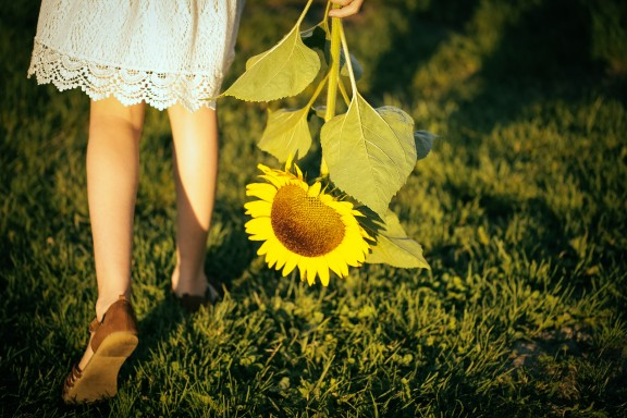 girl walking with a single sunflower