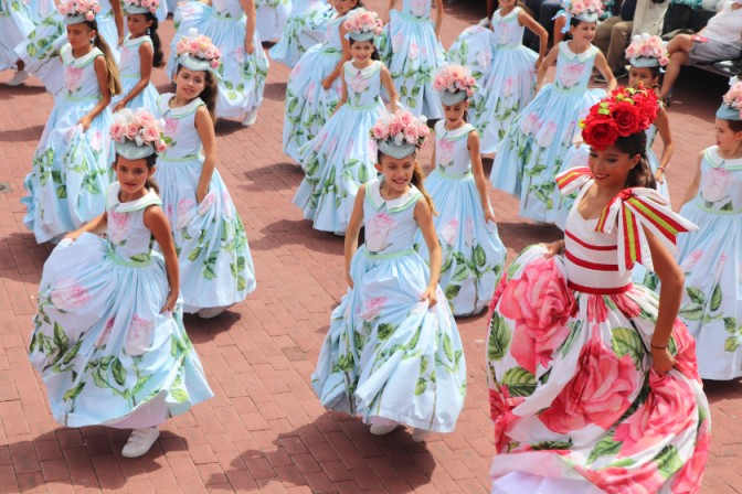 girls dancing with flowered hats at one of the most beautiful flower festivals in the world
