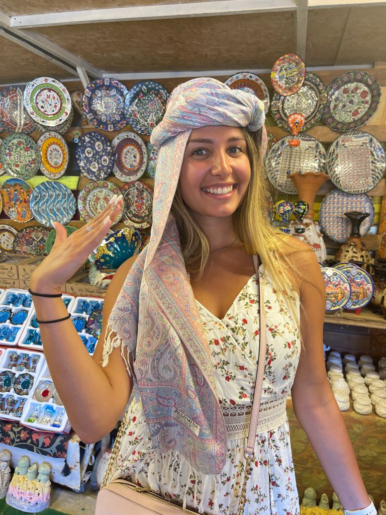 lady modeling a Pashmina head scarf souvenir of Turkey in a gift shop