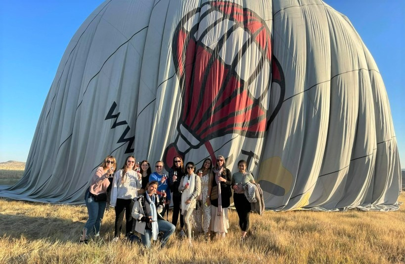 tour group posing in front of hot air balloon on the ground in cappadocia turkey