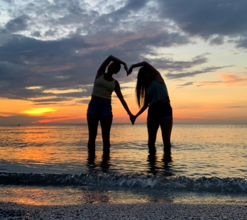 2 people forming a heart at sunset on the best beach in cleveland ohio - edgewater beach