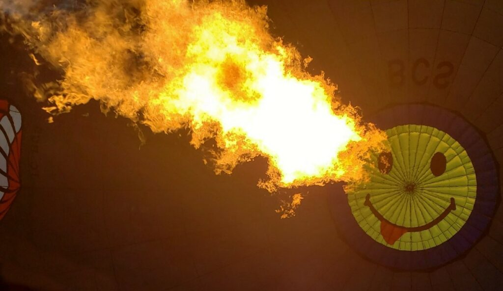 Fire heating up the cappadocia hot air balloon with smiley face on it