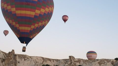 several hot air balloons floating over the Cappadocia landcape during hot air balloon rides in Turkey