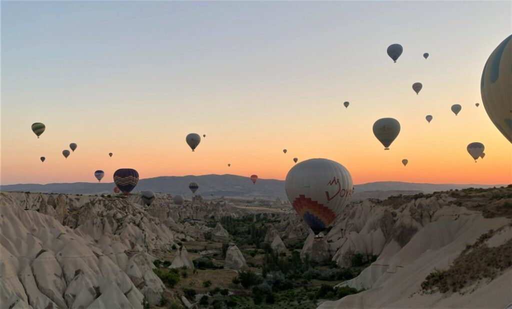 lots of hot air balloons floating throught the valley in Cappadocia Turkey