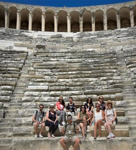 group sitting on seats at Aspendos Theater during one of the best small group tours in Turkey