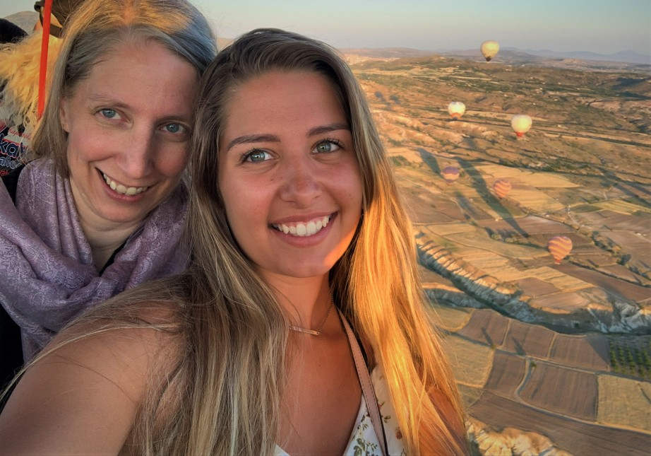 mother daughter pose in hot air balloon basket with balloon in the background in cappadocia turkey