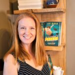 guest post Liz Alden stands in front of bookshelf - contributed to Books Set in Ohio