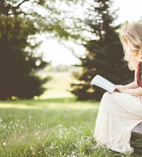 Girl Reading a book in ohio in a field